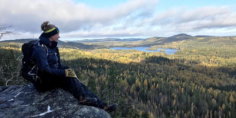 Vildmarksguiden Saana Lappalainen sitter med rinkan på ryggen på en hög klippa i Koli. Till höger öppnar sig ett skogslandskap.