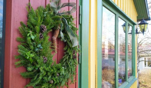 Den färdiga kransen av granris hänger på en röd ytterdörr.
