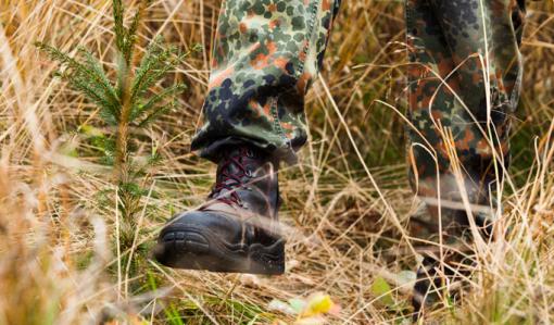 Närbild på de stadiga kängorna när en person trampar ner gräs runt en planta.