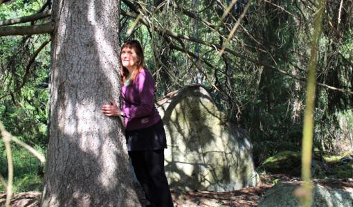 Kirsi Salonen står och lutar sig mot en trädstam, en gammal gran. Solstrålar sipprar in mellan grenverken.