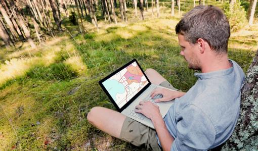 En man sitter på en gräsmatta med en dator i famnen och tittar på information om sin egen skog i e-tjänsten MinSkog.fi. Han lutar sig ryggen mot ett träd. Runt honom syns gräsmatta och i bakgrunden skog.
