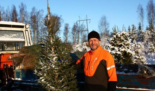 Antti Heikkilä står och håller i en julgran ute på vintern. Bakom honom syns en liten traktor och en ellinje.