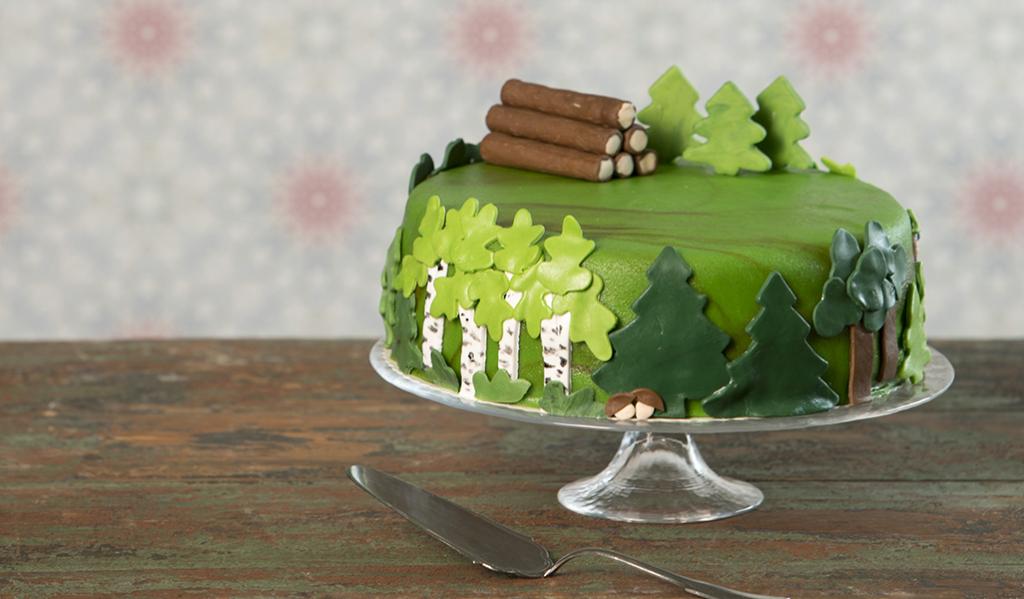 Tårtan är helt täckt av grön marsipan och garnerad med gran- tall- och björkfigurer av marsipan längs sidorna. Uppe på kakan ligger en timmerhög av marsipan, och bakom den står några marsipangranar.