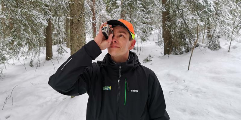 Skogsrådgivaren Ari Kasanen står i en snöig skog och håller en höjdmätare framför ögat.