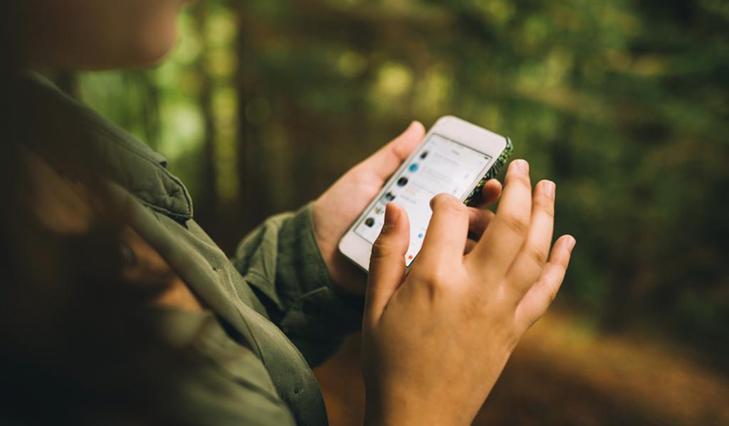Kuvituskuvassa henkilö selaa älypuhelinta ja somekanavia.