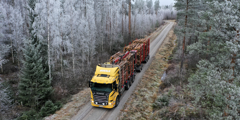 En virkestransportbil har fotograferats uppifrån. Fordonet har gul för och är fullastat. Skogsvägen som fordonet kör på kantas av skog.