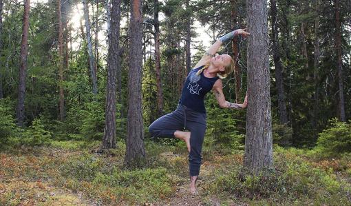 Eva Travanti leder ett skogsyogapass. Hon står på ett ben och tänjer sidan medan hon tar stöd med häönderna mot en tall.
