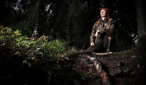 Viltplaneraren Teemu Lamberg sitter med ena knät i marken vid rötterna av ett träd. Skogen bakom honom är mörk.