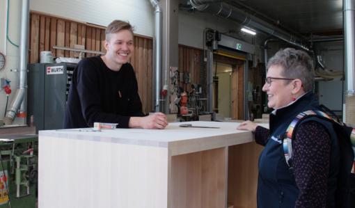 Miikka Kotilainen står bakom ett högt bord av trä och pratar med företagsrådgivare Leila Laukkanen i Puuartistis produktionslokal.