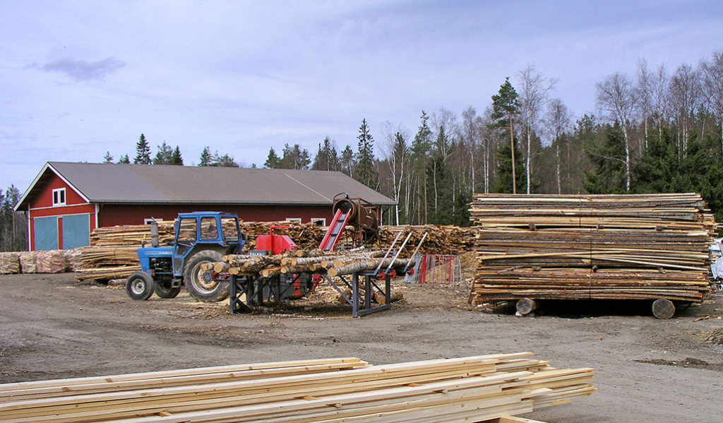 På gården till Kolkonjoen saha kör en traktor och på marken står sågvaror staplade.