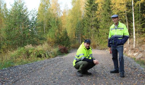 Tomi Vähä-Kouvola sitter på huk på en skogsväg. Bredvid honom står Tapio Kahilaniemi. Gula löv har fallit på vägen, som omges av skog.