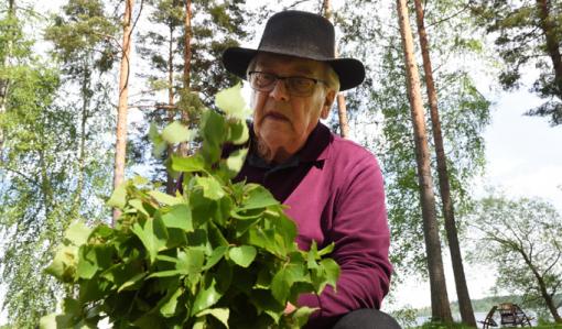 En man sitter utomhus och tillverkar en bastukvast av björkris.