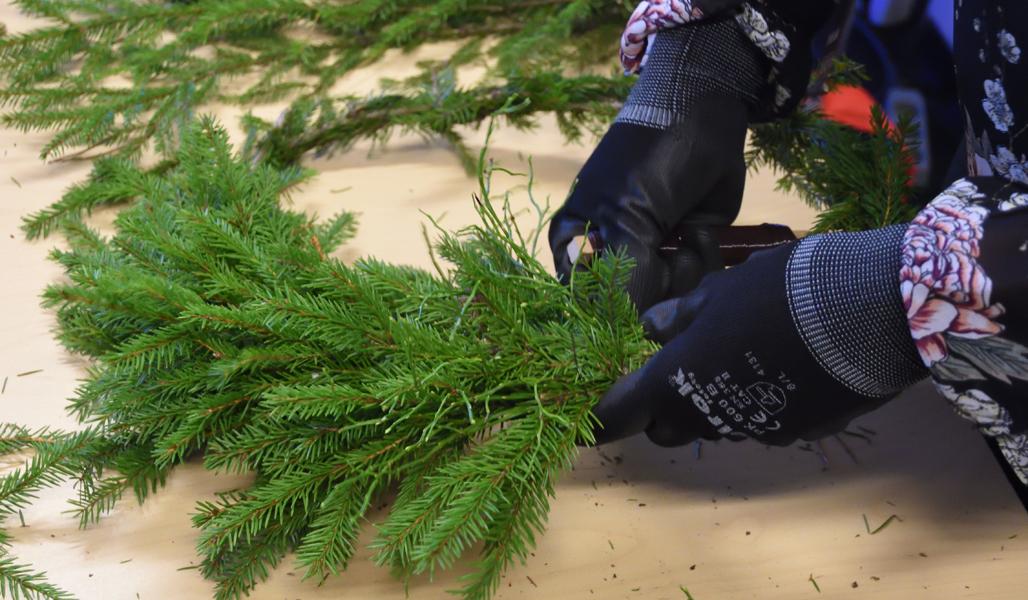 Närbild på granrisknippen som fästs på kransstommen. I knippena har man lagt till blåbärsris.Kranssiin kiinnitetään havunippua, johon on lisätty mustikanvarpuja.