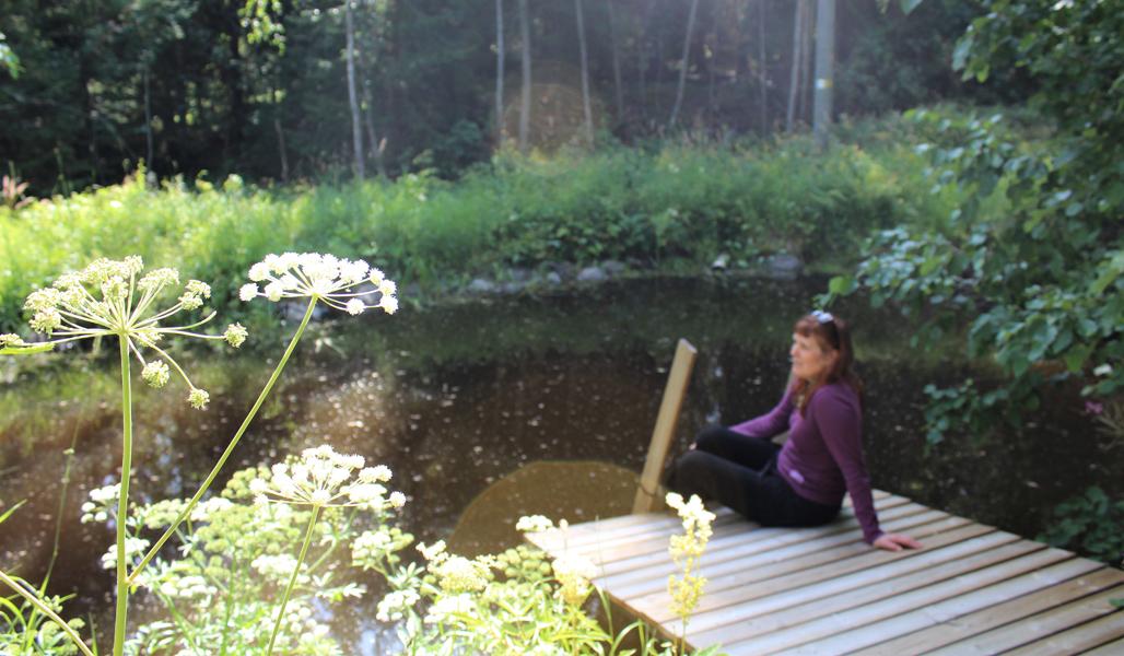 Kirsi Salonen istuu lammen rannassa laiturilla.