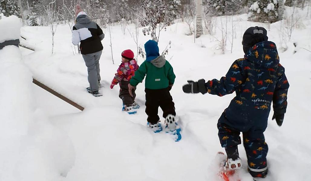 En vuxen och tre barn går med snöskor i snön.