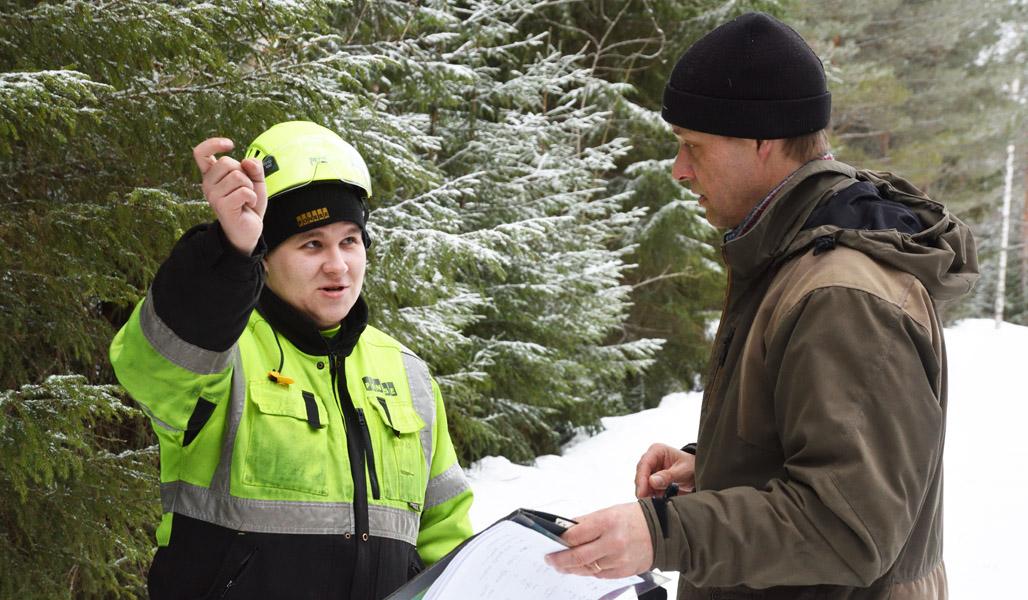 Skogsmaskinsföraren Mikko Inkinen och Jukka Ruutiainen står och samtalar på en skogsväg. Bakom dem syns snöiga granar.