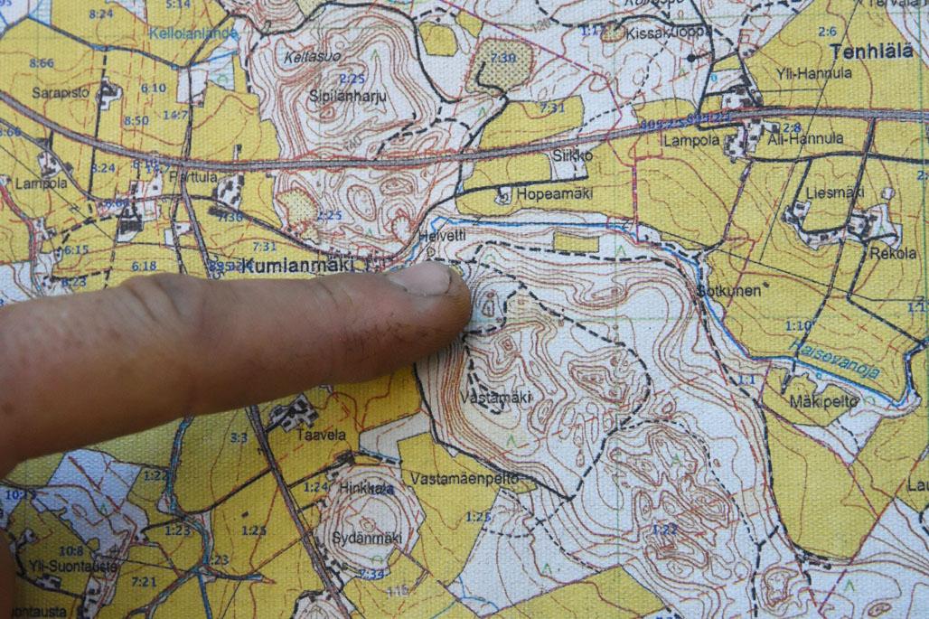 Närbild på ett finger som pekar på området i Hämeenkoski där det hittats spillning av flygekorren.