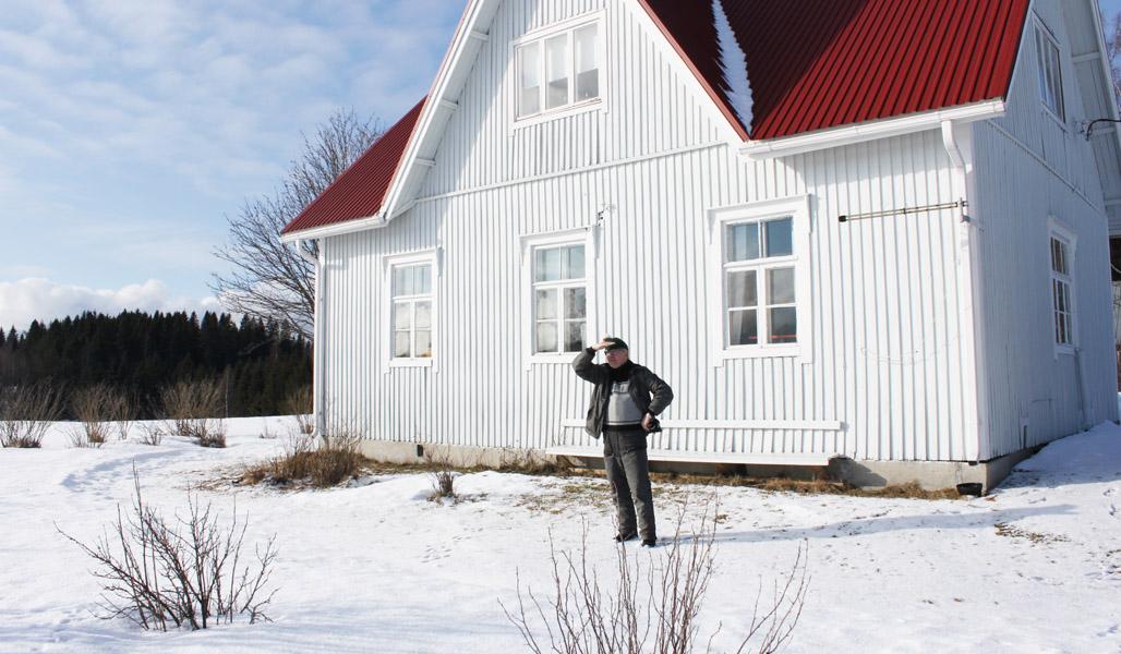 Timo Nissinen står framför huset som är släktens sommarviste och spanar ut mot skyddsobjektet. Det är snö på marken, i bakgrunden syns buskar på gården och längre bak skog.