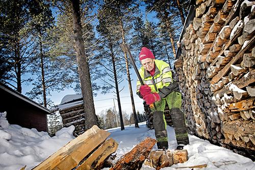 Marjatta Kyllönen hugger ved ute på vintern. Bredvid henne står en vedstapel.