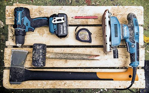 Marjatta Kyllönens arbetsredskap uppradade på en pall, t.ex, en borrmaskin, en tummermanspenna, ett måttband, en slipmaskin, en klubba och en yxa.