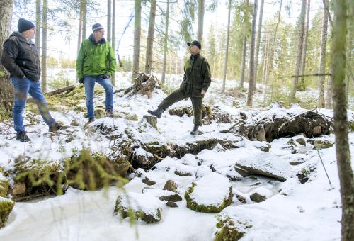 Visa Mikkola, Pentti Pakarinen och Mika Tuomola står och pratar invid en bäck i naturtillstånd. Det är snö på marken.