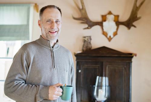 Skogsägaren Mika Tuomola stående i sitt hem med kaffekopp i handen. Vid väggen bakom honom står ett brunt skåp och på det en prydnadsuggla. På väggen hänger ett par älghorn.
