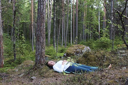 Elina Iivonen ligger på rygg under en tall med händerna på magen.