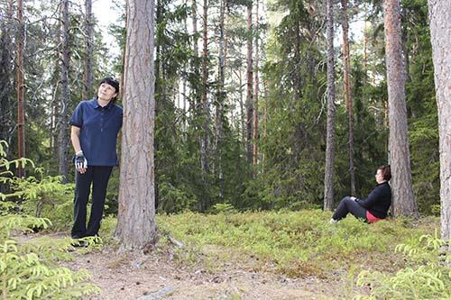 Mari Jussila står och lutar sidan mot en tall. Minna Sundman sitter en bit därifrån och lutar ryggen mot en tall.