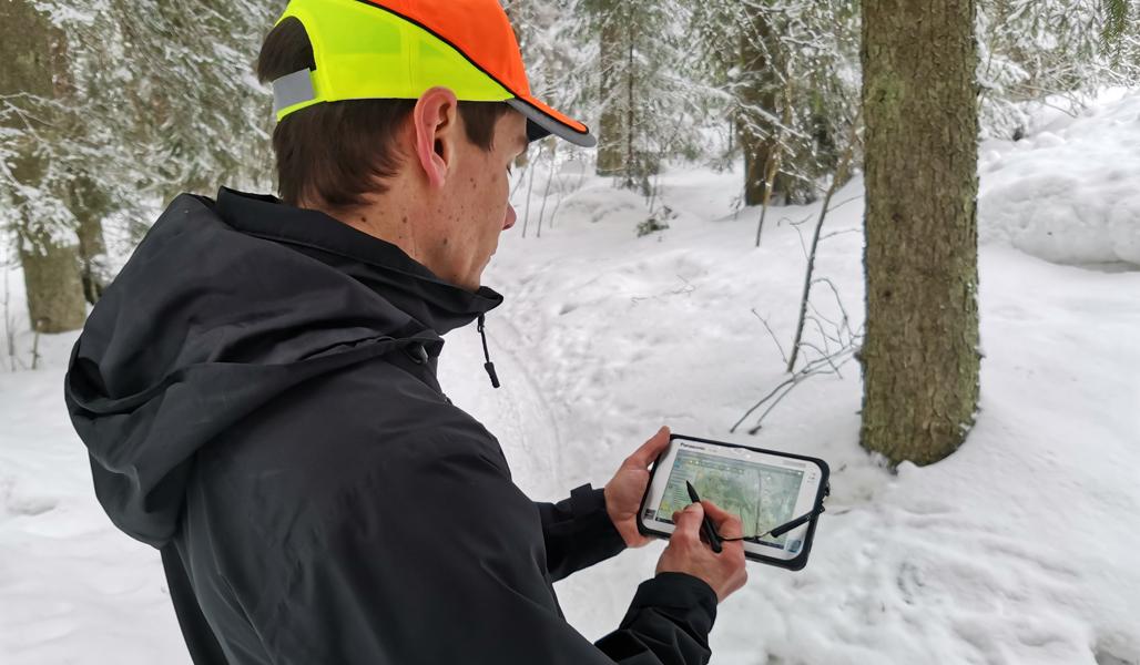 Ari Kasanen kontrollerar information på fältdatorn som han håller i handen i en vintrig skog.