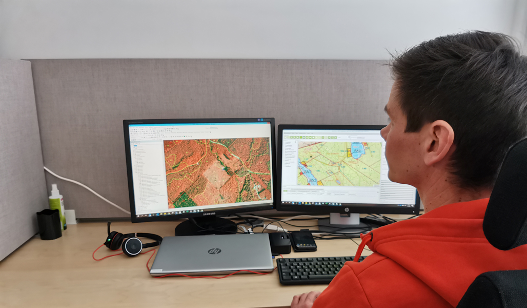 Ari Kasanen tittar på kartbilder på två datorskärmar vid sitt arbetsbord.