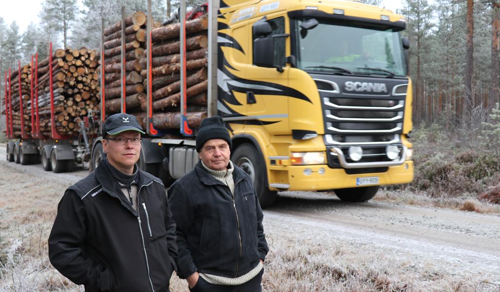 Kuvassa ovat Sammuksen tiekunnan puheenjohtaja Jouni Mäkiluoma (vas.) ja hoitokunnan jäsen Juhani Kosola. Heidän takanaan on tukkirekka.