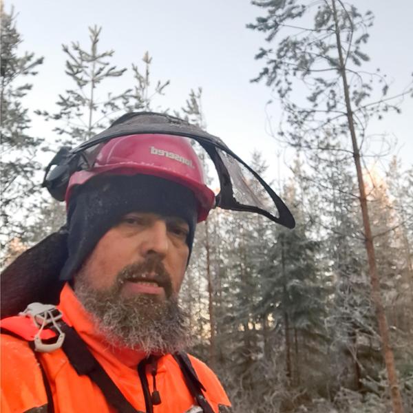 Juhani Toivakka har fotograferat sig själv i skogsarbetarhjälm i skogen på vintern.