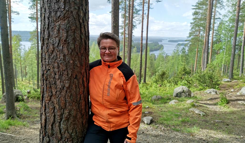 Anne Ruokonen står bredvid en tall. Bakom henne syns skog och ett insjölandskap.