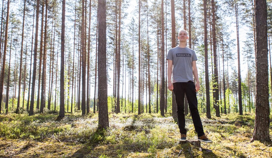 Miikka Kotilainen har fotats i en ekonomiskog bestående till stor del av tall.
