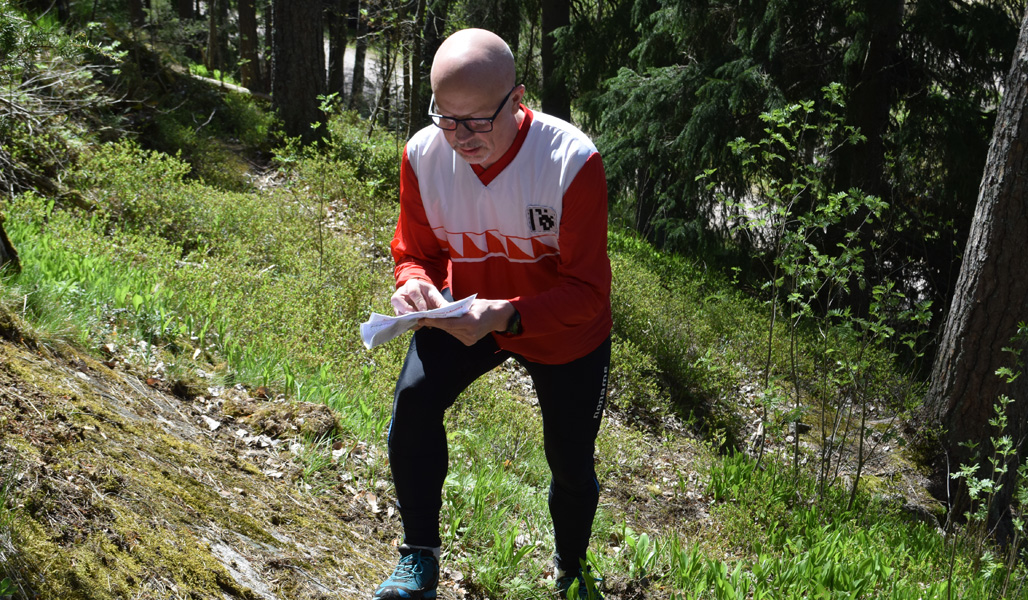 Jyrki Ahvonen står i skogen och tittar på kartan.