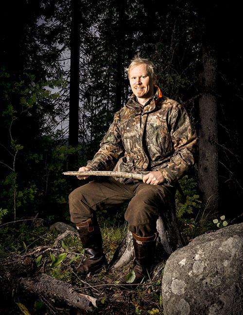 Viltplaneraren Teemu Lamberg sitter på en stubbe och ler. I händerna håller han en liten trädgren. Skogen bakom honom är mörk.