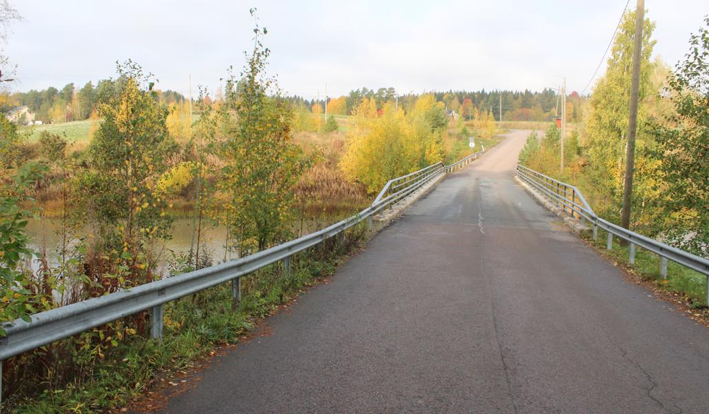 Kuvassa on asvaltoitu yksityistie ja silta, joka ylittää joen. Ympärillä on syksyistä maaseutumaisemaa.