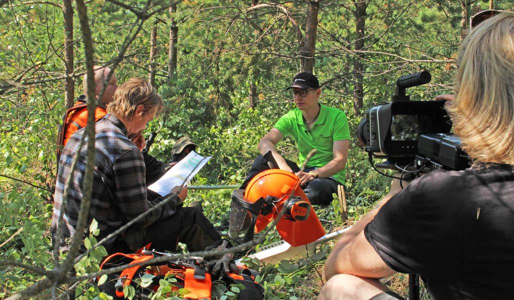 Roope Tonteri, metsuri Ari Oinas ja metsäneuvoja Henri Hiltunen kuvaustauolla metsässä.