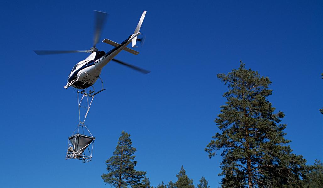 En flygande helikopter mot en blå himmel. Under helikoptern hänger kärlet med askgödsel som sprids i skogen.