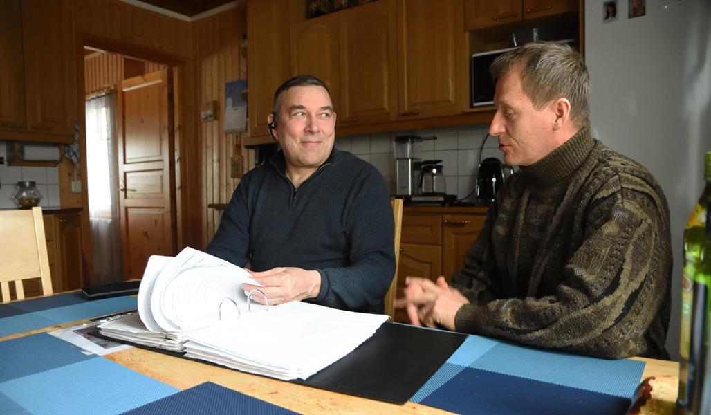 Ari Sirviö och Markku Remes sitter vid köksbordet med en pärm med papper.